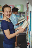 Smiling schoolgirl reading book in library at school. Portrait of smiling schoolgirl reading book in library at school Royalty Free Stock Images