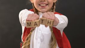 Smiling schoolgirl showing at camera math word on wooden cubes, exact sciences. Stock footage stock footage