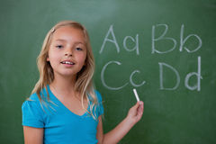 Smiling schoolgirl showing letters Stock Photo