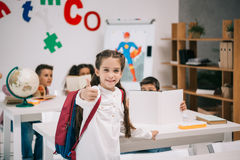 Smiling schoolgirl showing thumb up while classmates studying behind royalty free stock images