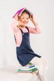 Smiling schoolgirl sitting on books Stock Image