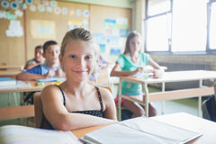 Smiling Schoolgirl Sitting in the Classroom Royalty Free Stock Image