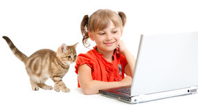 Smiling schoolgirl sitting at notebook with kitten Royalty Free Stock Photography