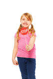 Smiling schoolgirl with small Stop sign icon. Close-up portrait of young fair-haired girl, holding small red Stop sign, isolated on white royalty free stock images