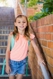 Smiling schoolgirl standing on staircase Stock Photos