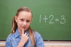 Smiling schoolgirl thinking Stock Photos