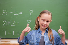 Smiling schoolgirl with the thumbs up Royalty Free Stock Image