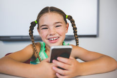 Smiling schoolgirl using mobile phone in classroom Royalty Free Stock Photo