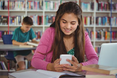 Smiling schoolgirl using mobile phone in library. At school Stock Photo