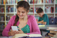 Smiling schoolgirl using mobile phone in library. At school Royalty Free Stock Photo