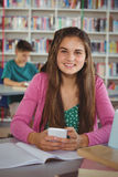 Smiling schoolgirl using mobile phone in library at school. Portrait of smiling schoolgirl using mobile phone in library at school Stock Photo