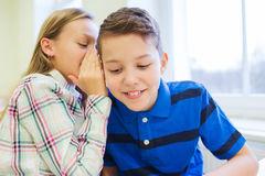 Smiling schoolgirl whispering to classmate ear Royalty Free Stock Images