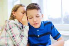 Smiling schoolgirl whispering to classmate ear Stock Image