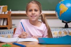 Smiling schoolgirl writing Stock Images