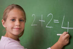 Smiling schoolgirl writing a number Stock Images