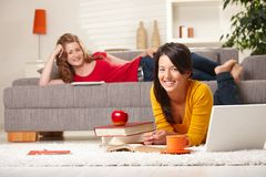 Smiling schoolgirls learning at home. Happy schoolgirls learning at home in living room with books and laptop, looking at camera smiling royalty free stock images