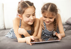 Smiling schoolgirls lying on couch and playing on tablet Royalty Free Stock Photography