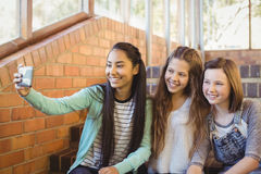 Smiling schoolgirls sitting on the staircase taking selfie with mobile phone Stock Photos
