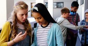 Smiling schoolgirls using mobile phone in corridor stock video