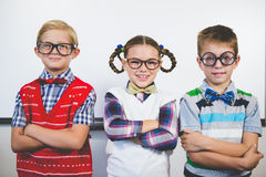 Smiling schoolkids standing with arms crossed in classroom Stock Photos