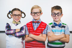 Smiling schoolkids standing with arms crossed in classroom Stock Photo