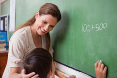 Smiling schoolteacher helping a schoolboy Stock Image