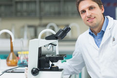 Smiling scientific researcher with microscope in laboratory Stock Image