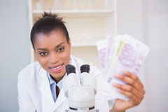 Smiling scientist holding money and looking at camera Royalty Free Stock Images