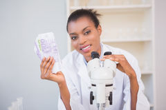 Smiling scientist holding money and looking at camera Stock Images