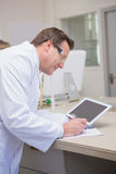 Smiling scientist holding tablet writing on notebook Royalty Free Stock Photo