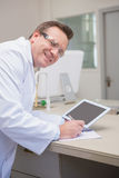 Smiling scientist holding tablet writing on notebook Stock Image