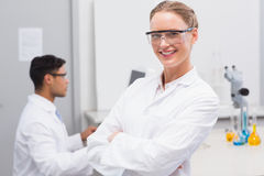 Smiling scientist looking at camera arms crossed. In laboratory Royalty Free Stock Images