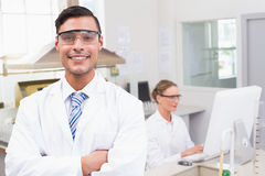 Smiling scientist looking at camera arms crossed. In laboratory Stock Photo
