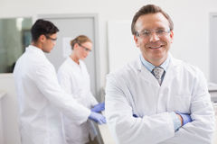 Smiling scientist looking at camera while colleagues working behind. In laboratory Stock Photography