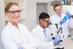 Smiling scientist looking at camera while colleagues working with microscope. In laboratory Royalty Free Stock Photography