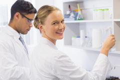 Smiling scientist looking at camera and holding a beaker. In laboratory Royalty Free Stock Photography