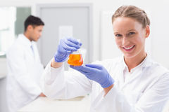 Smiling scientist looking at camera and holding beaker with orange fluid. In laboratory Royalty Free Stock Photography