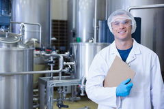 Smiling scientist looking at camera holding a clipboard. In the factory Stock Image