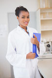 Smiling scientist looking at camera and holding file Stock Images