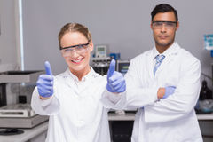 Smiling scientist looking at camera thumbs up with her colleague behind. In laboratory Royalty Free Stock Photography