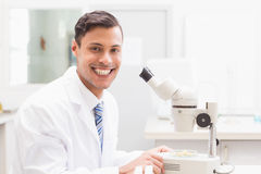 Smiling scientist observing petri dish with microscope Royalty Free Stock Photography