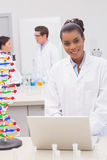 Smiling scientist using laptop while colleagues talking together Royalty Free Stock Photos