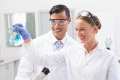 Smiling scientists looking at beaker Stock Photos