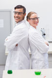 Smiling scientists standing back to back. In laboratory Stock Images