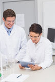 Smiling scientists using tablet Royalty Free Stock Images