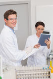 Smiling scientists using tablet Stock Photos
