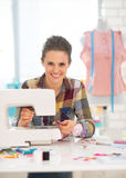 Smiling seamstress sewing in studio Stock Photo