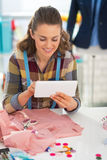 Smiling seamstress using tablet pc at work Royalty Free Stock Images