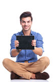 Smiling seated man showing the screen of his tablet. Young smiling seated man showing the screen of his tablet pad computer on white background Royalty Free Stock Photography