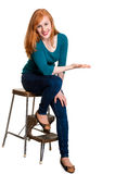 Smiling seated redhead, indicating space for text Stock Photography